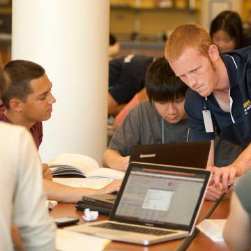 Male student directing other students grouped around a table