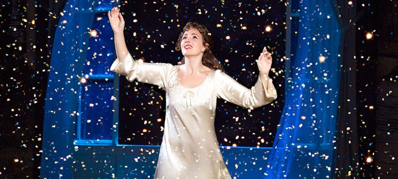 A young woman cast member smiling onstage with her hands raised, surrounded by fairy dust.