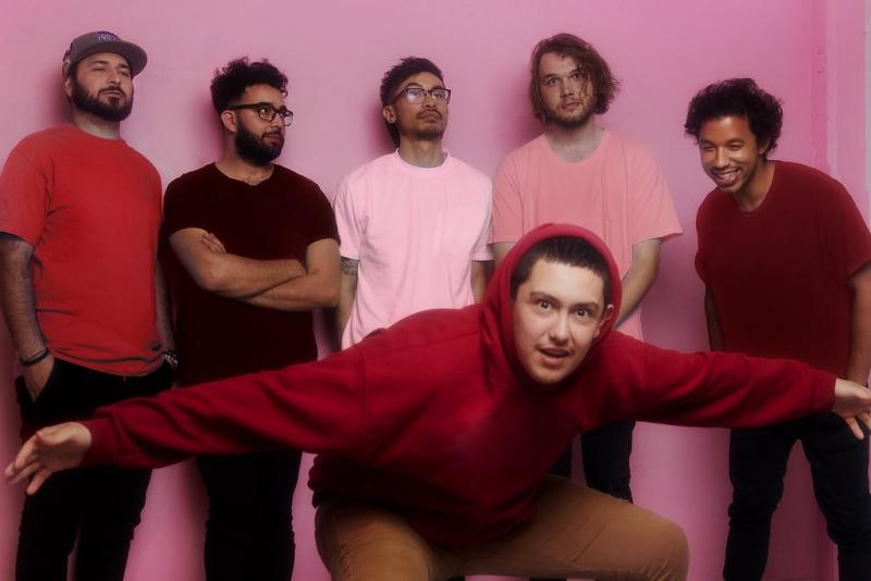 A photo of the group in front of a pink wall.