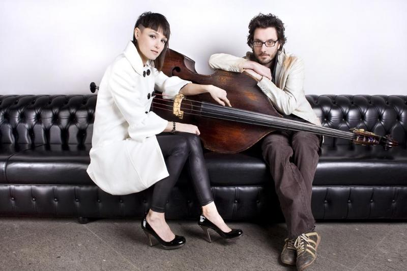 The two members of the group sitting on a black leather couch with a double-bass.