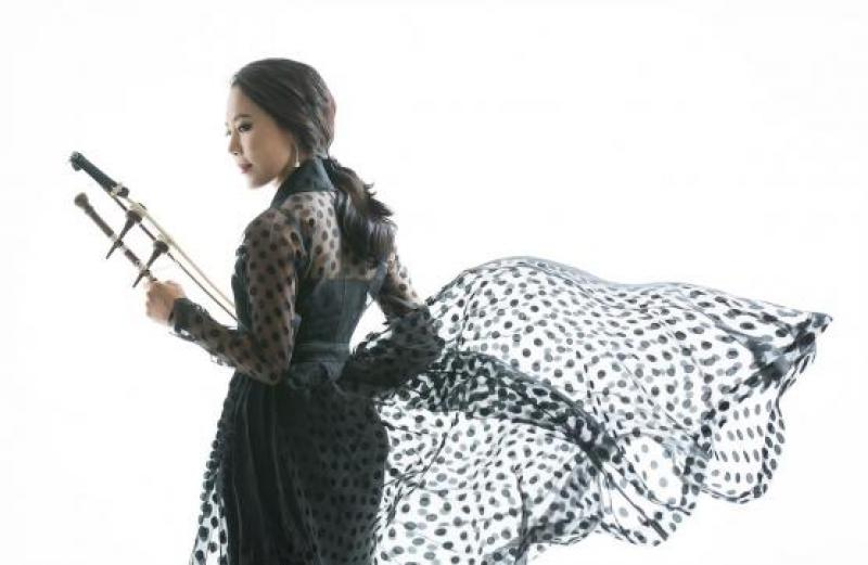 Soo-Yeon Lyuh holding her haegeum, her polka-dot skirt blowing in the wind.