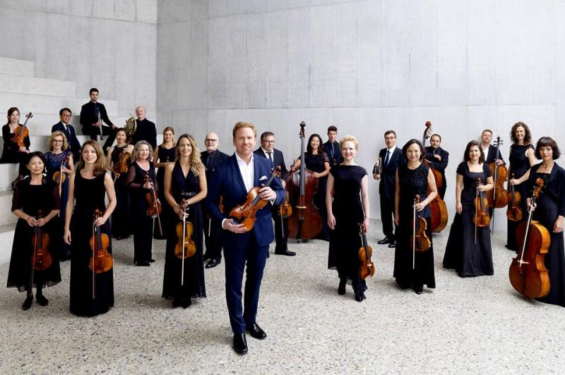 The orchestra members standing in a marble-clad room holding thier instruments.