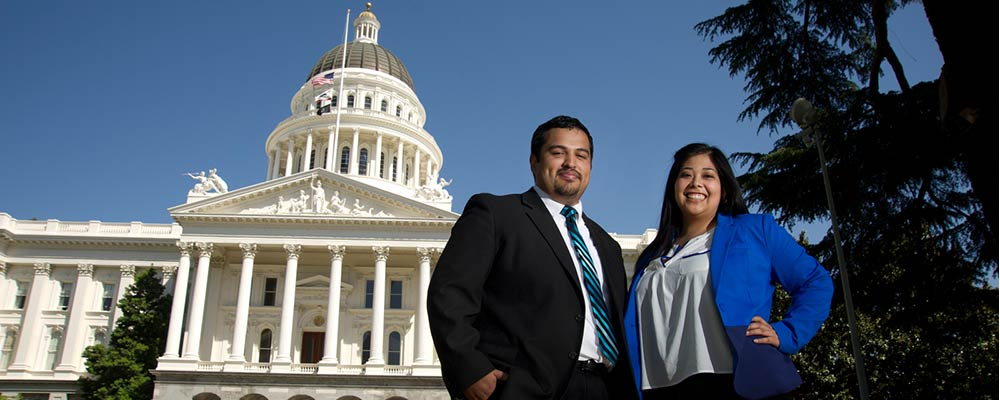 Two people in work attire posing in front of the California State Capitol