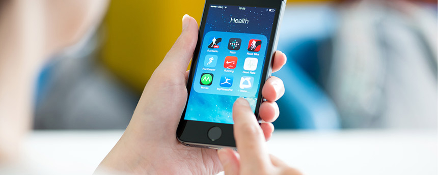 Woman's hands hold cell phone with health apps on screen.