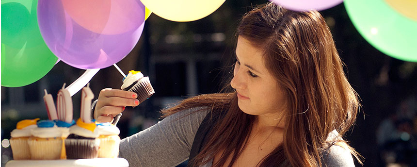 Young woman picks up frosting-covered cupcake.