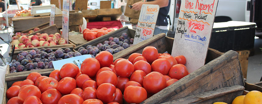 Wooden boxes of tomatoes, plums and apples displayed at a farmers market.