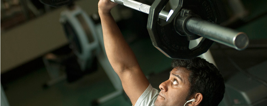 Male college student looks up at weight he is lifting.