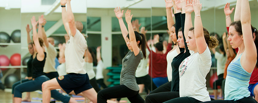 Female students and others in yoga class lunge forward with arms raised.